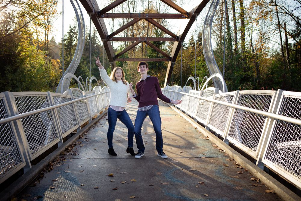 brother and sister being posing silly on a bridge