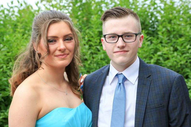 teenage couple pose in the garden for a prom photograph