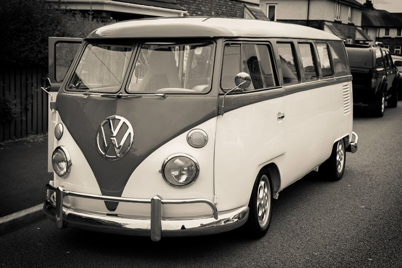 old style vw camper van parked up ready to take the young couple to the prom