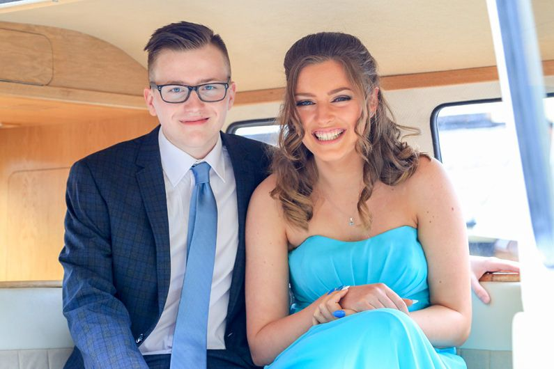 couple smiling pose for a photograph inside the vw camper van