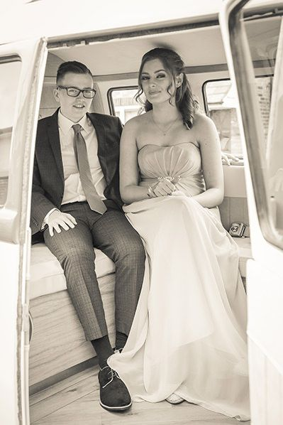 young couple photographed inside the vw campervan through the open door