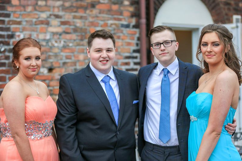 2 young couples pose for a photograph at their school prom