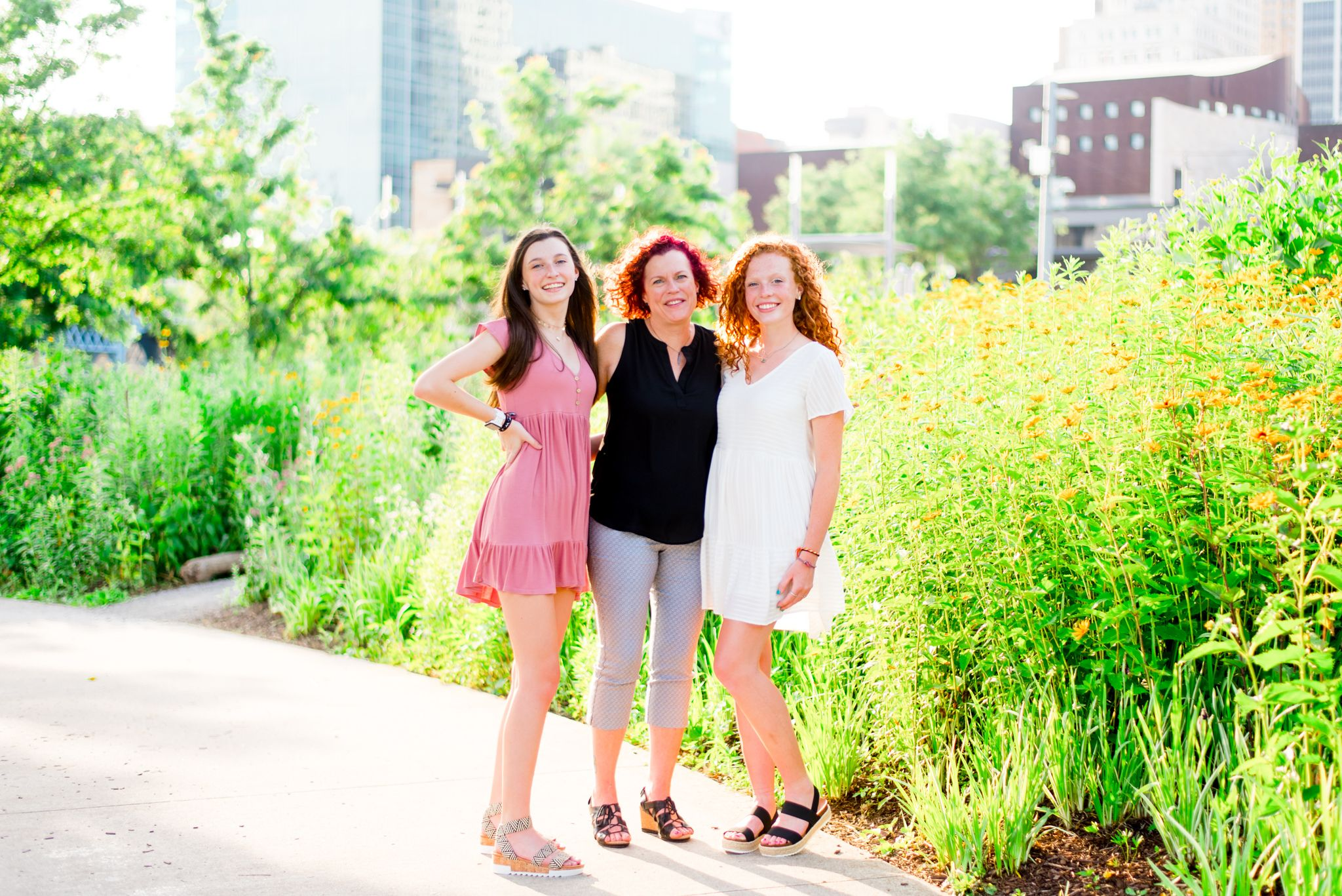 mom and two teenage daughters smiling in Smale Park in front of flowers and buildings