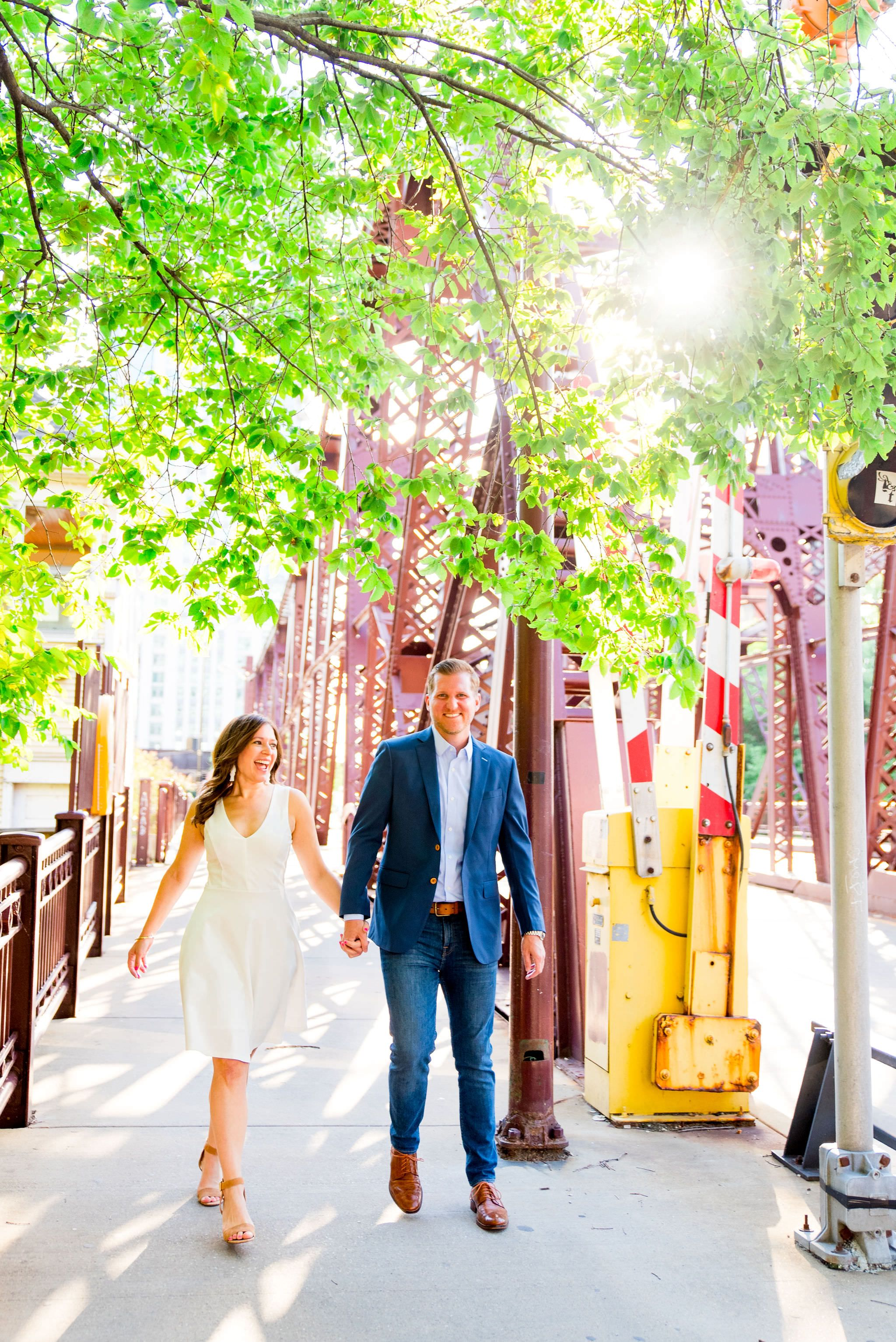 woman in white dress and man in navy suit walking by Kinzie St Bridge in Chicago for sunset engagement pictures