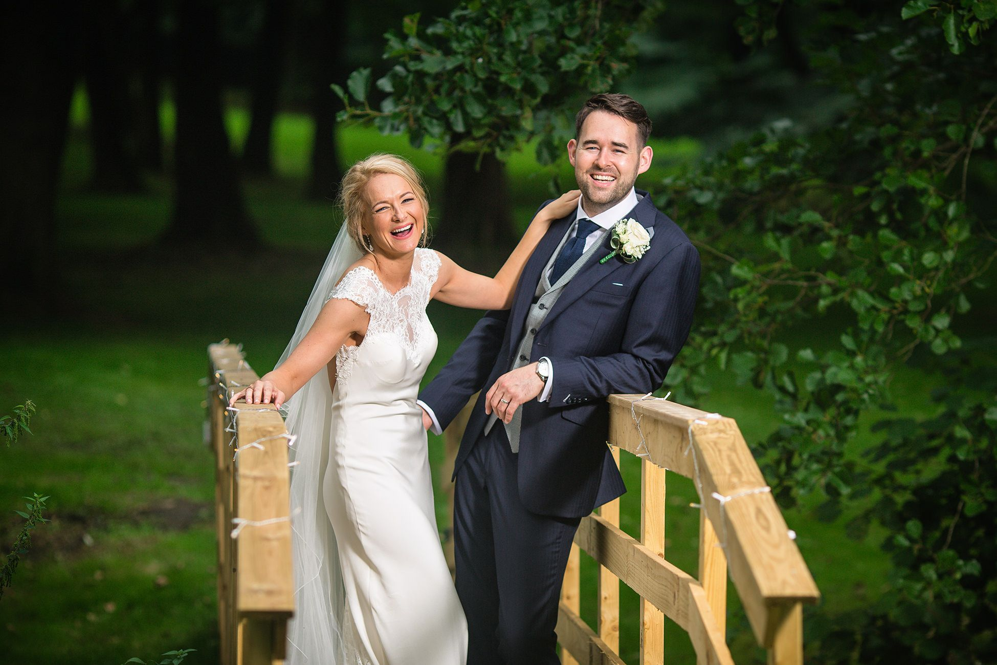 Bride and groom stand laughing on a wooden bridge in the garden of their Cheshire Marquee wedding