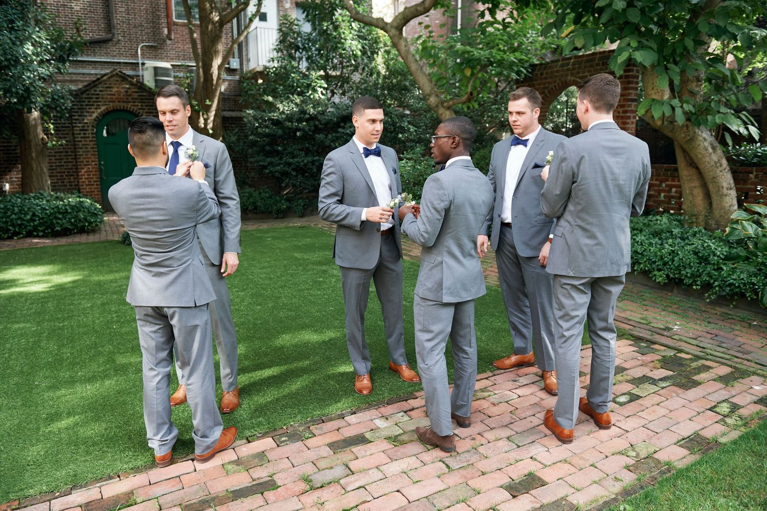 groomsmen trying to put on boutonnieres at Colonial Dames in Philadelphia