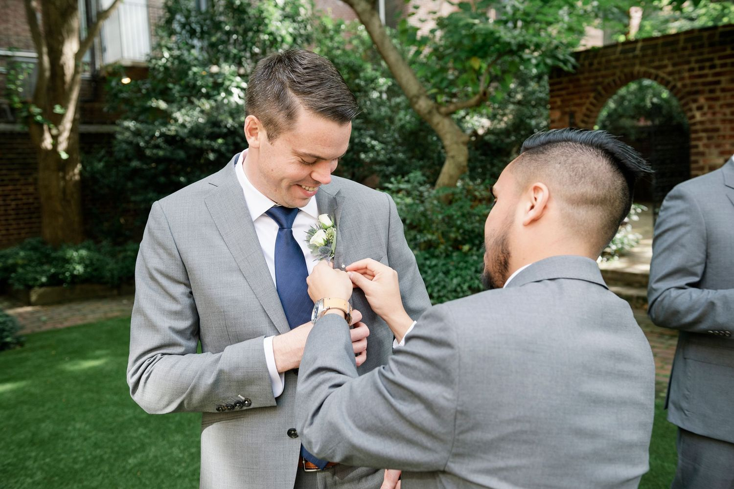 groom getting help with boutonniere at Colonial Dames in Philadelphia