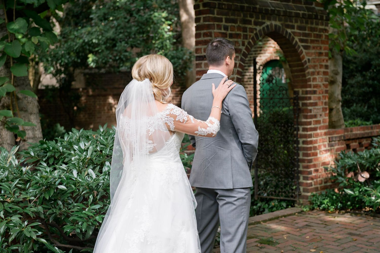 bride taps groom on shoulder during first look at Colonial Dames in Philadelphia