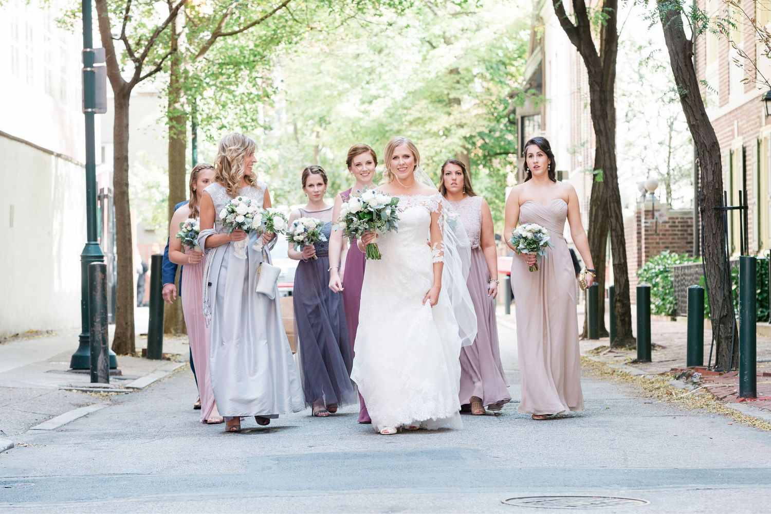 bride and bridesmaids walking in the street on way to the church