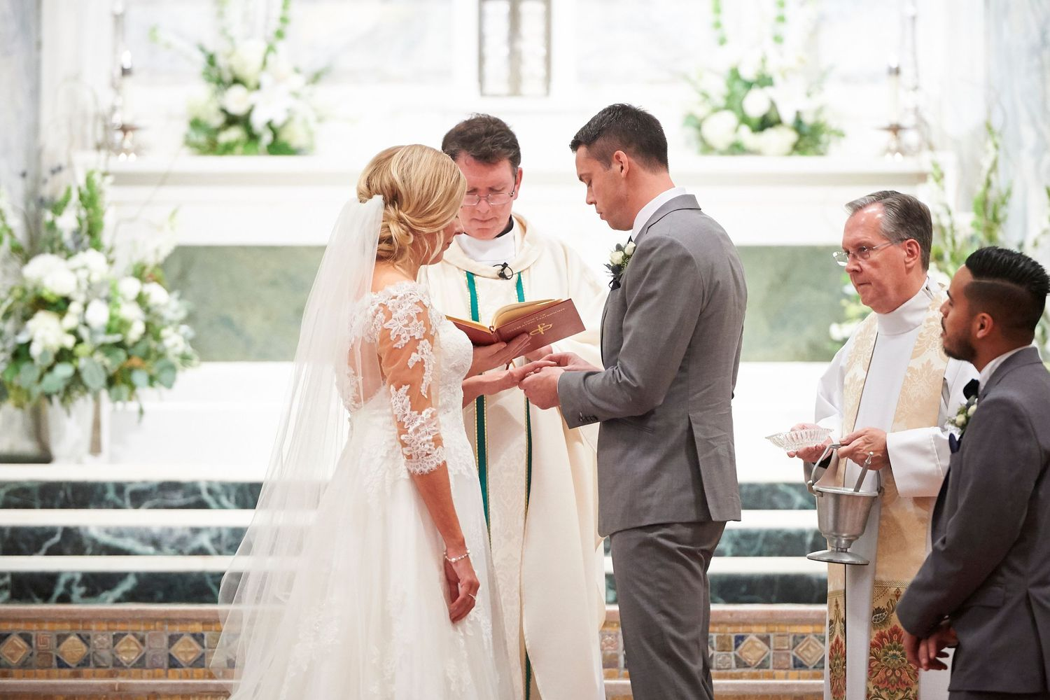 groom placing ring on bride's hand during ceremony at St. Patrick's Church