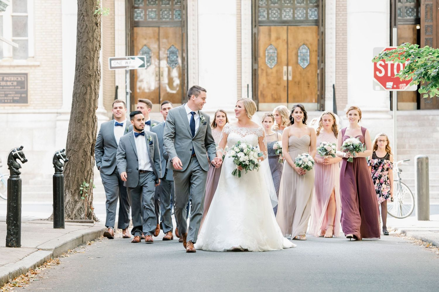 bride and groom and bridal party walking the streets of Philadelphia after wedding