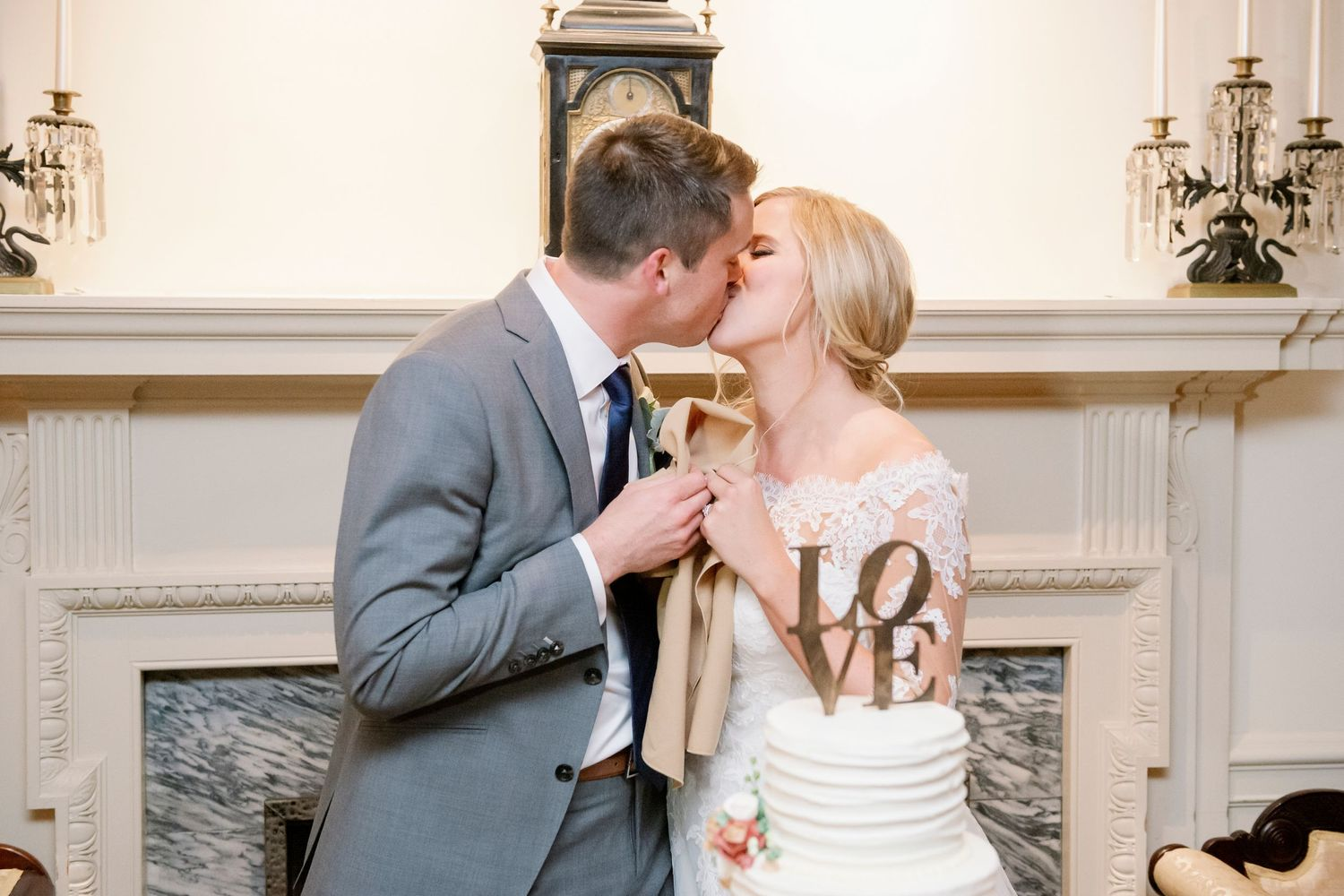 bride and groom kiss after cutting cake at Colonial Dames in Philadelphia