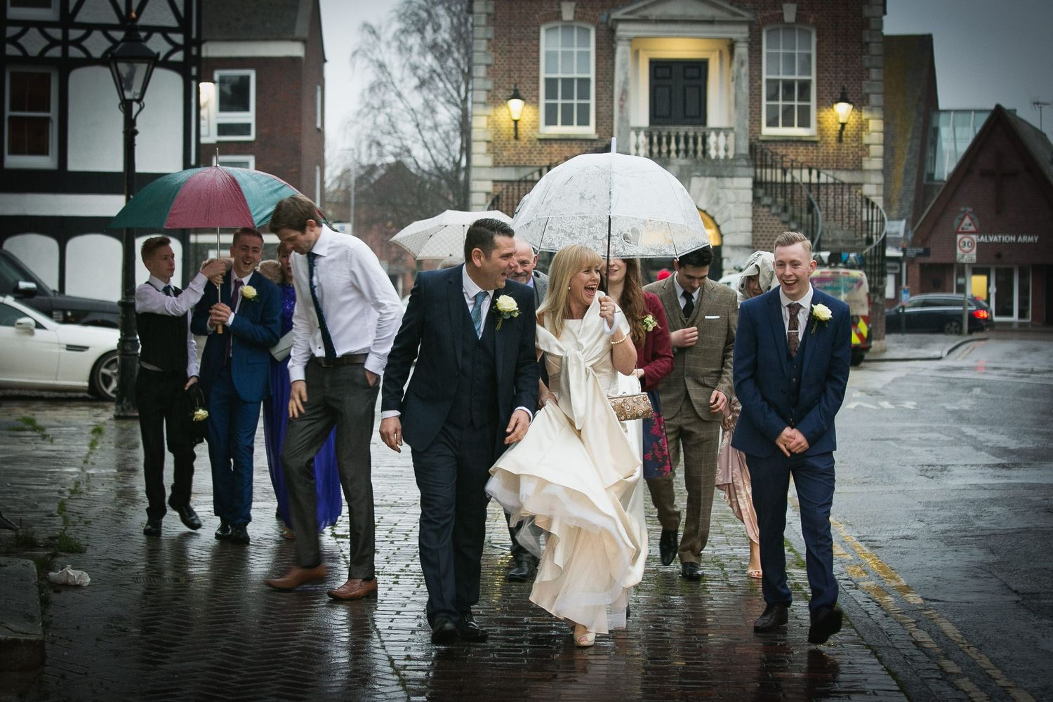 Bride and groom lead their guests through the rain on Poole Quay
