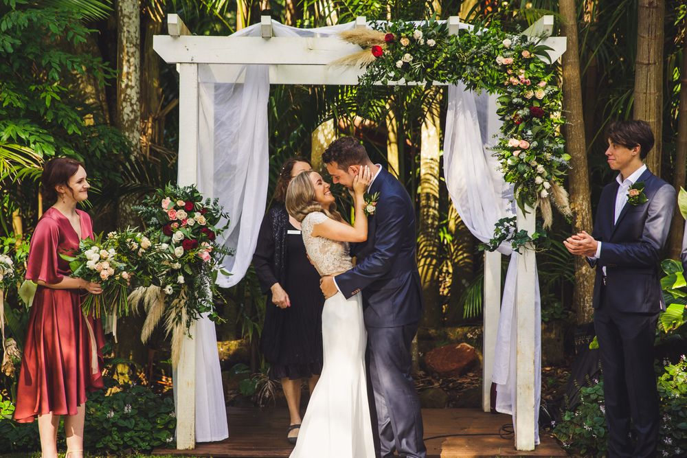 Bride and Groom's first kiss under floral arbour