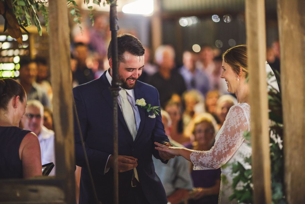 Bride and groom exchanging rings in barn wedding ceremony