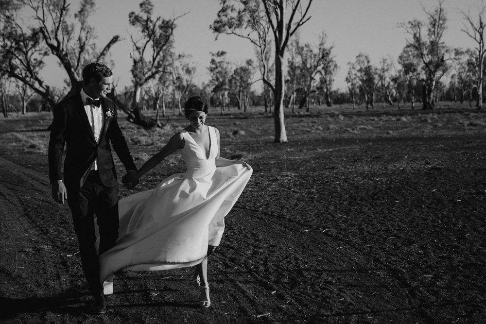 Bride and groom walking through family farm