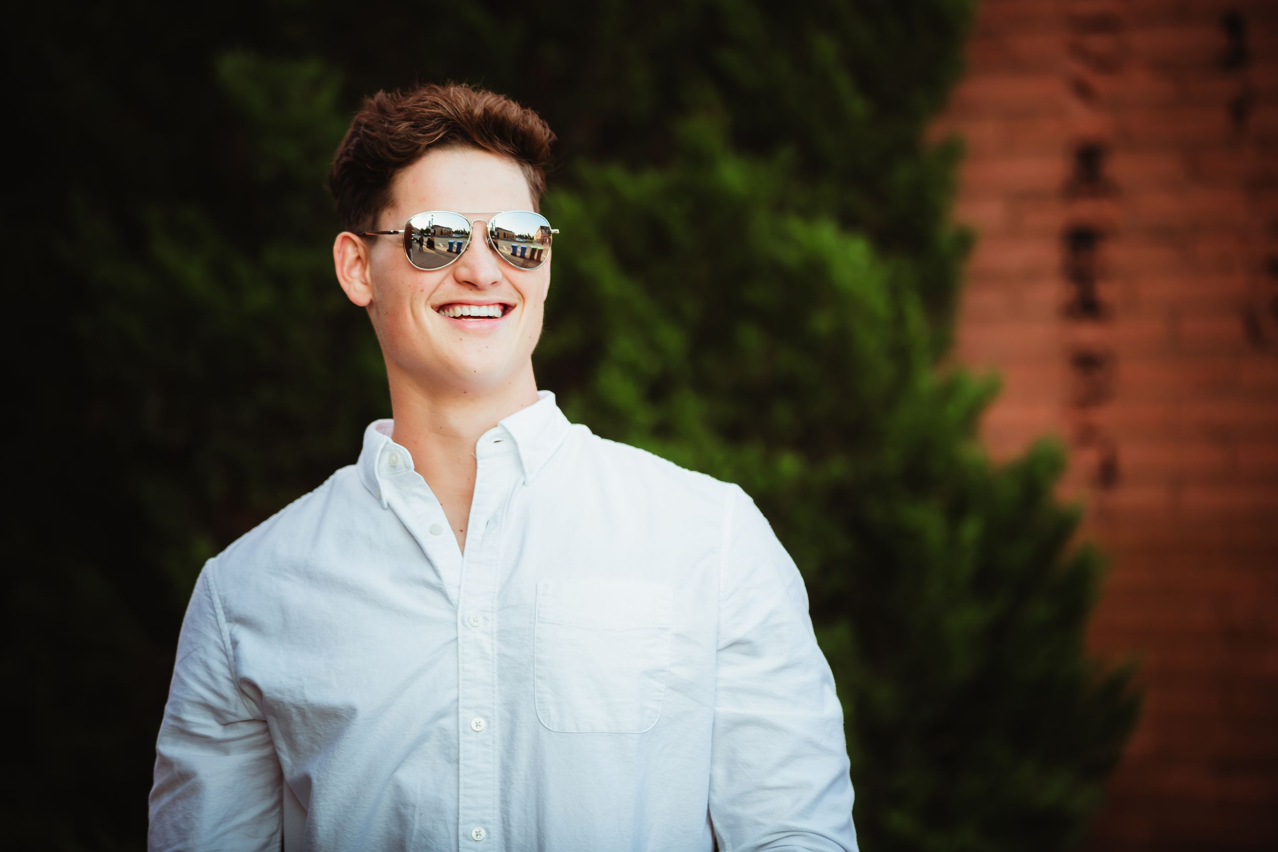 Close up of a high school boy smiling to his left wearing a white button up shirt and reflective aviator sunglasses.