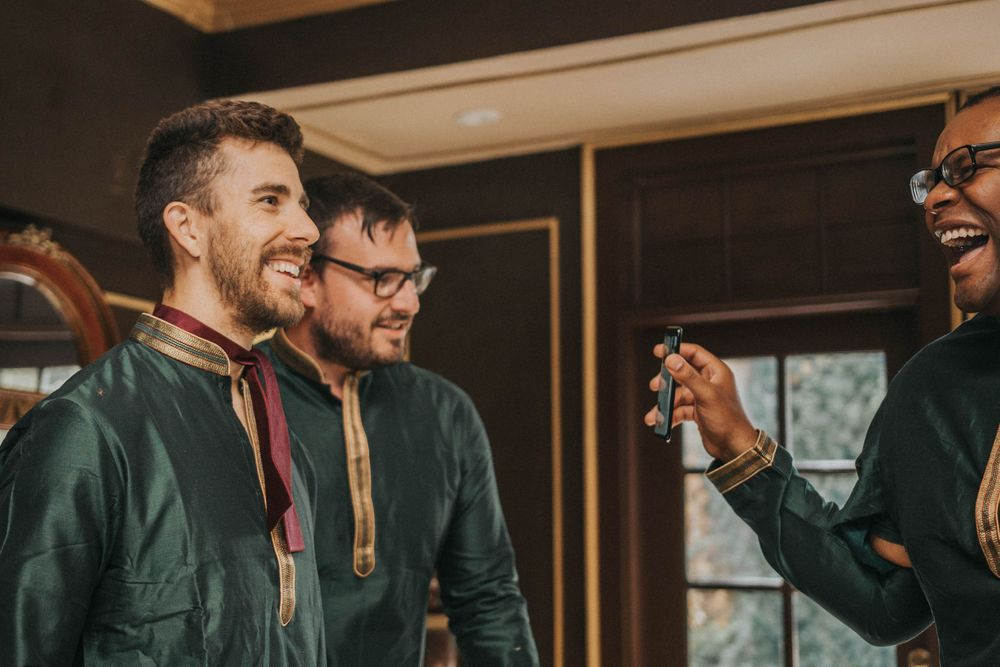 rebecca skidgel photography grand island mansion indian wedding groomsmen being goofy getting ready