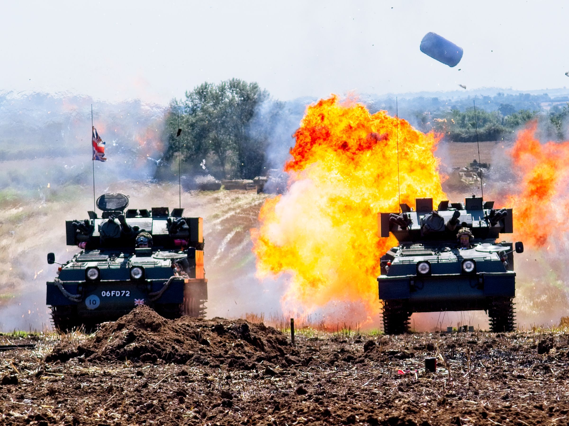 tanks, trucks & firepower 2019 armoured vehicles drive through explosions with balls of fire around one vehicle