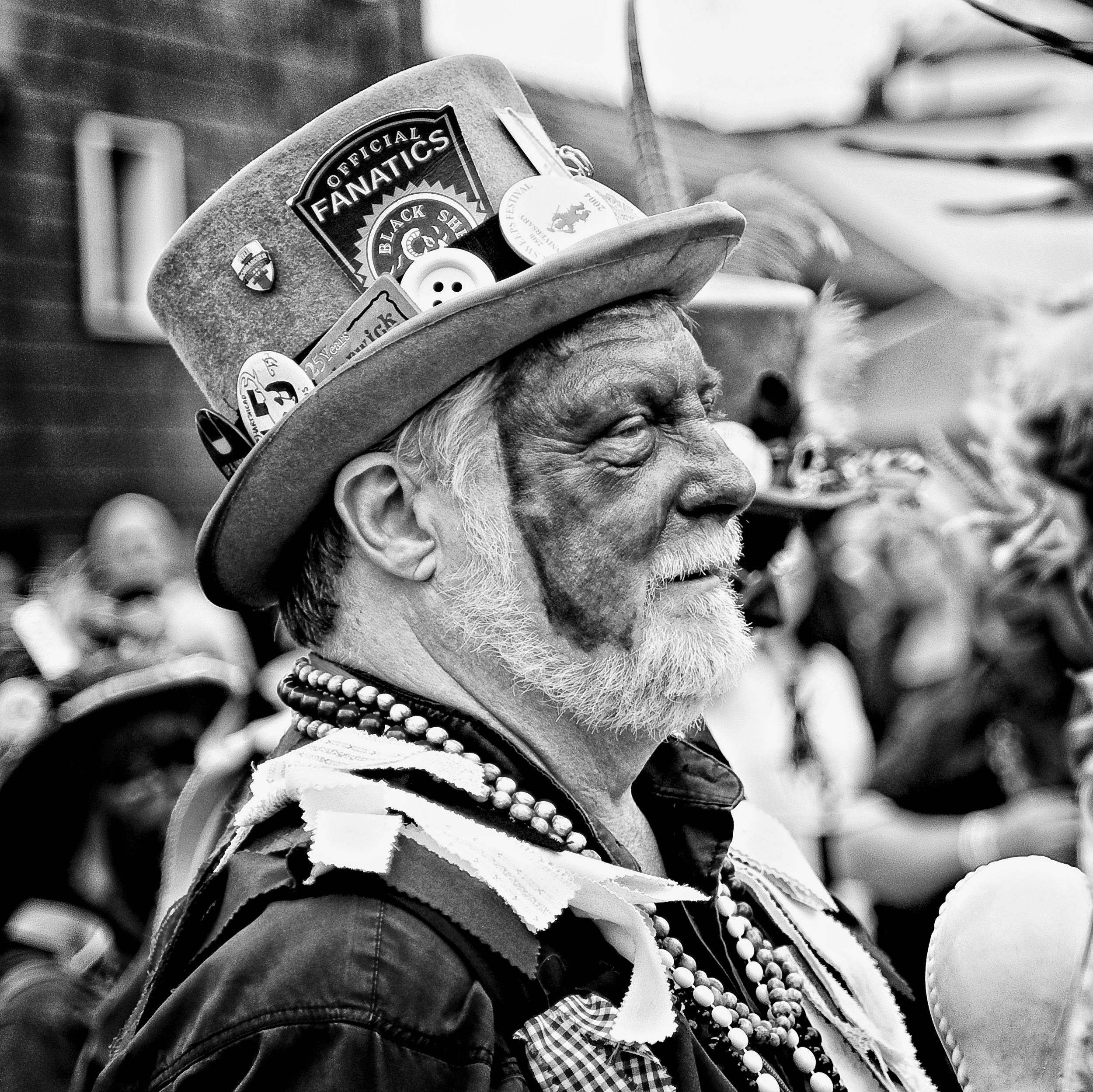 warwick folk festival black and white image of a male wearing a top hat with badges on it