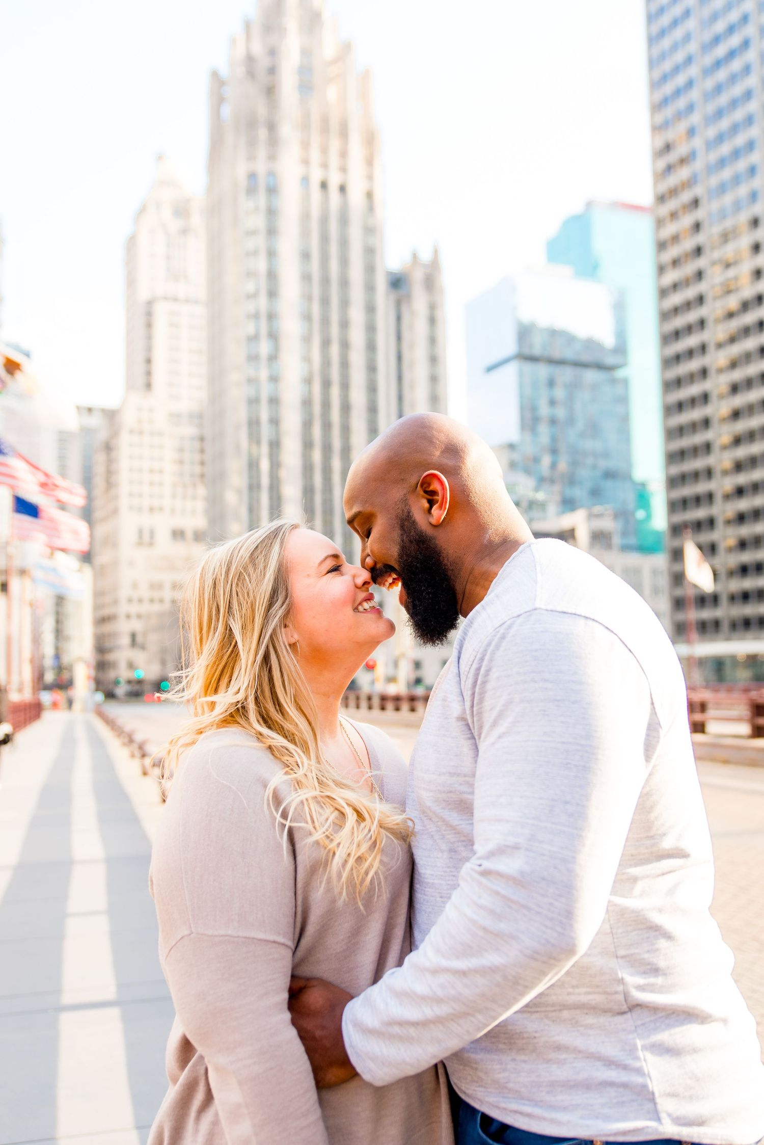 man and woman laughing in Chicago engagement photos in downtown Chicago near Wrigley Building
