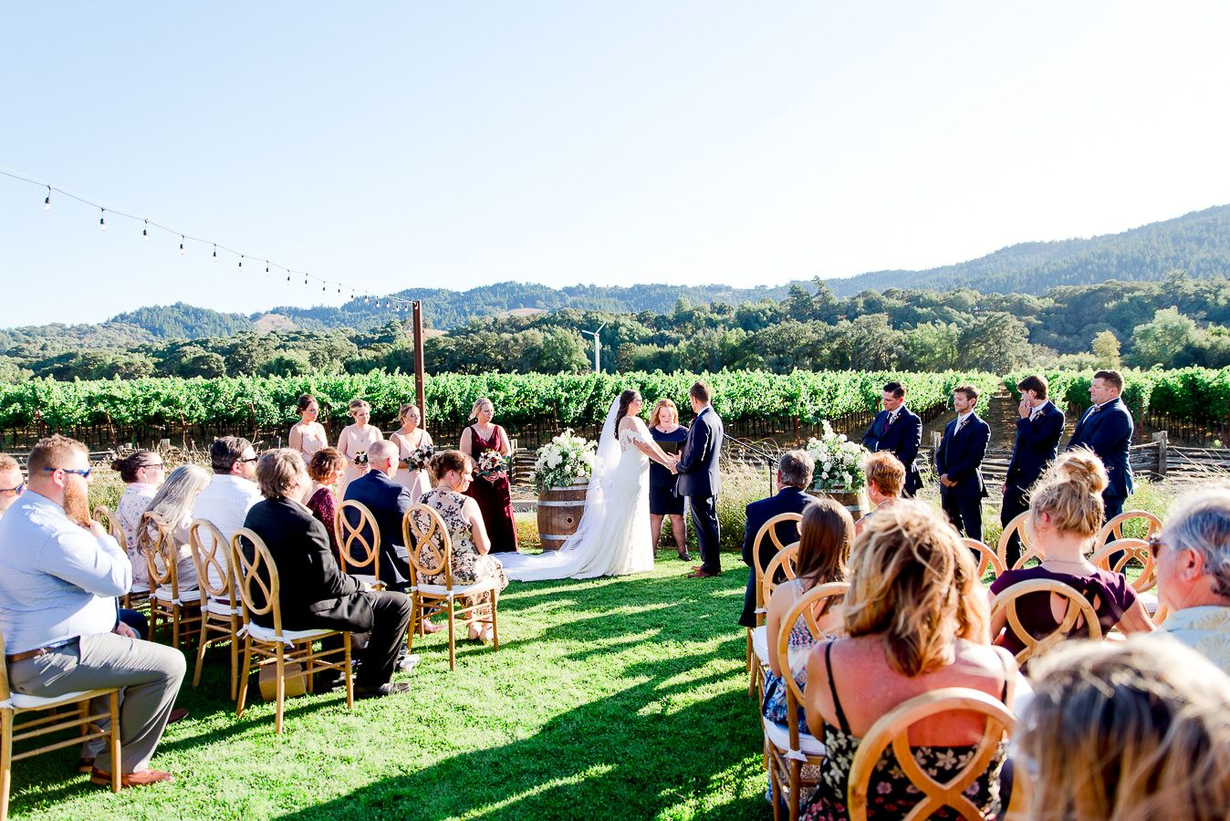 bride and groom hold hands in front of guests for outdoor wedding at Pennyroyal Farm in NorCal