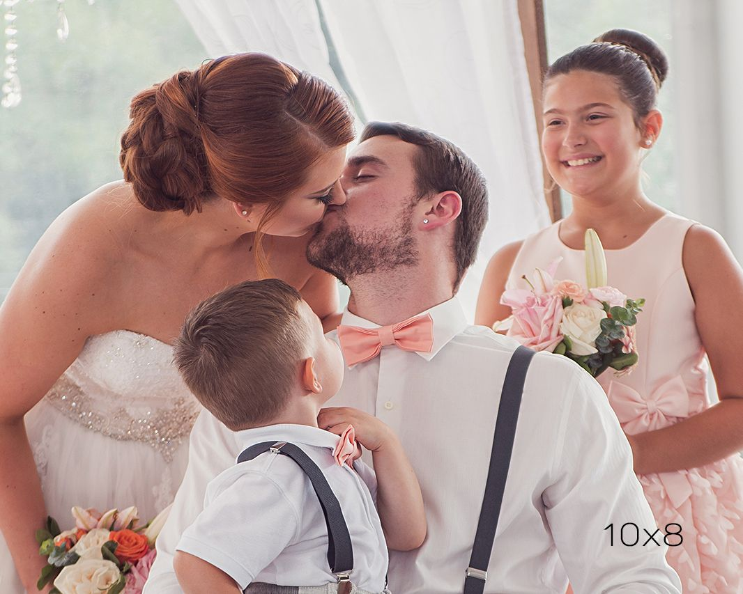 10x8 crop image of bride and groom kissing while children look on