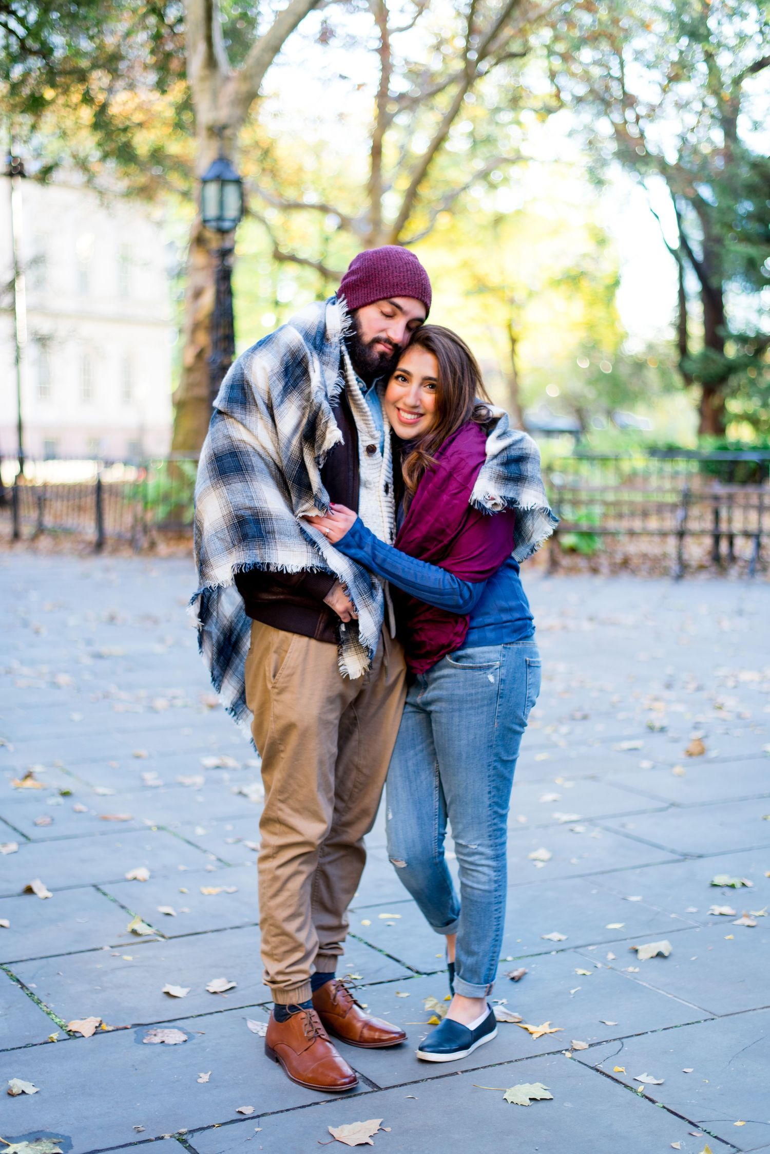 engaged woman hugs her fiance and smiles for November engagement pictures in New York City