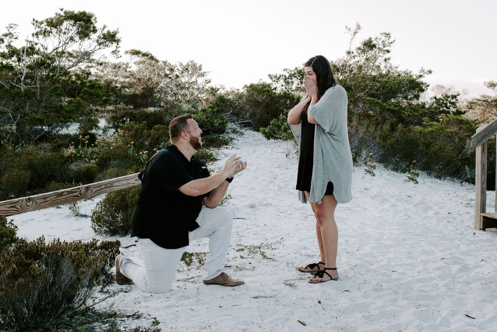 man proposing to his girlfriend at Henderson Beach state park