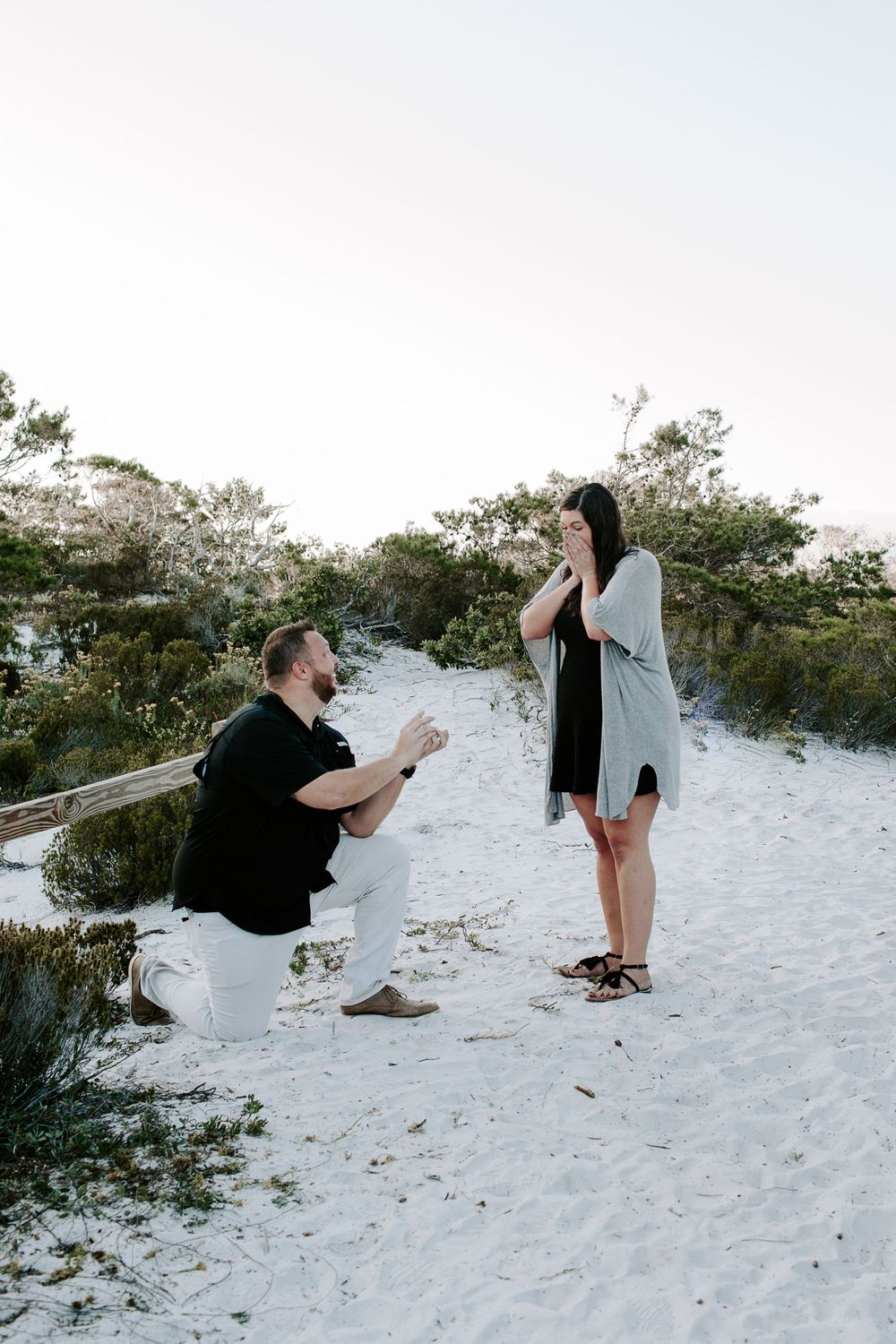 surprised woman looking at her fiancé proposing to her during their Florida proposal