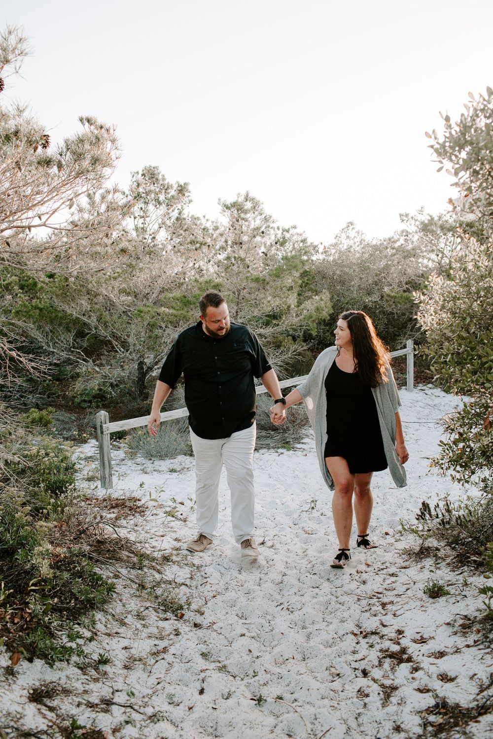 man and woman holding hands at Henderson Beach State Park during their Florida photoshoot