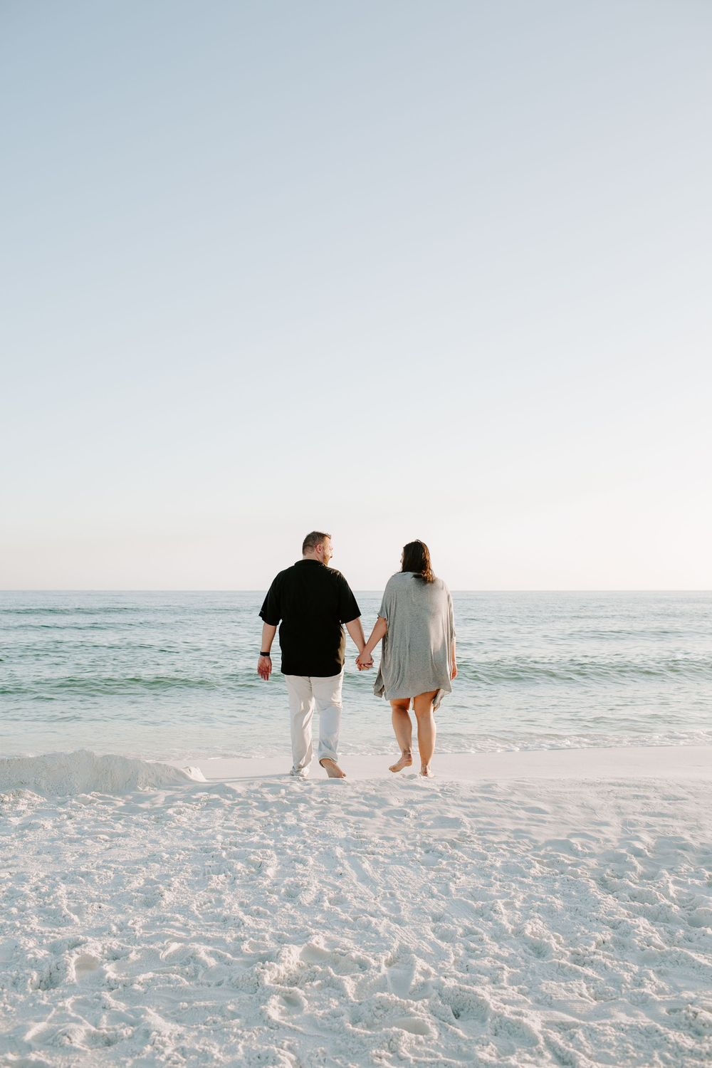 men and woman holding hands walking towards the ocean during their beach photoshoot