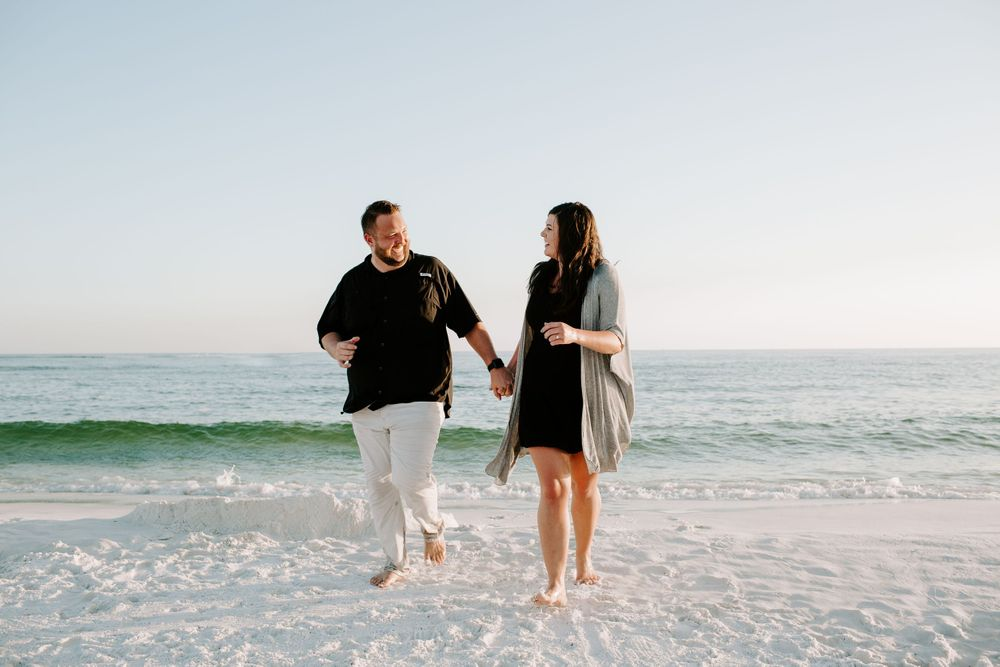 man and woman holding hands running along the beach during their Destin vacation