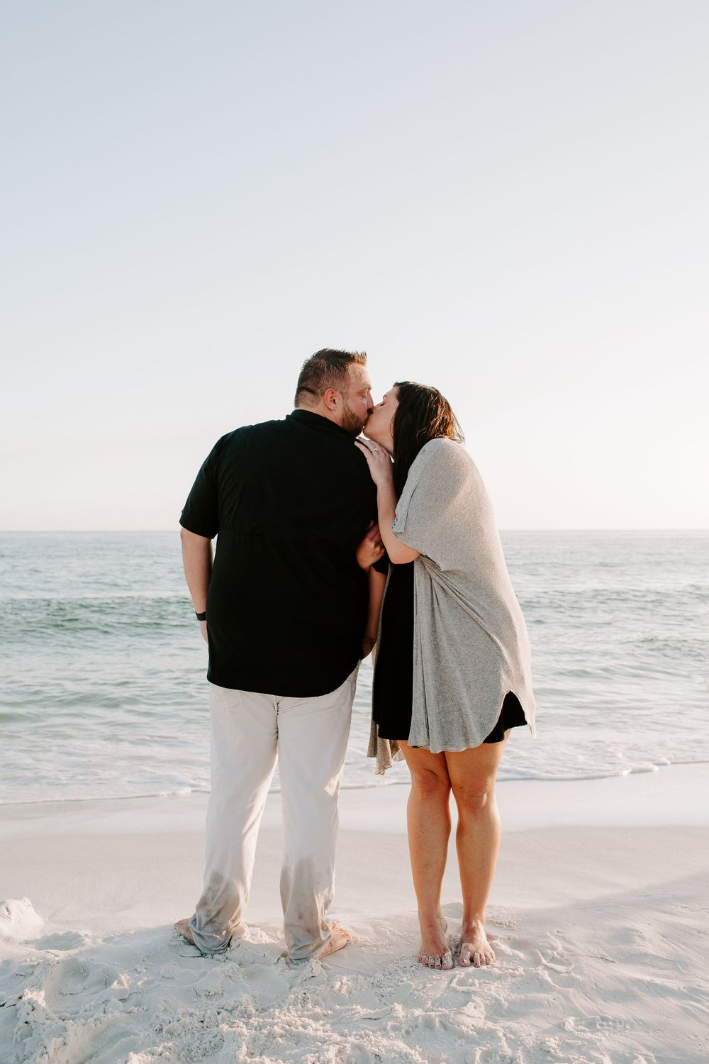 man and woman kissing on the beach after their beach proposal