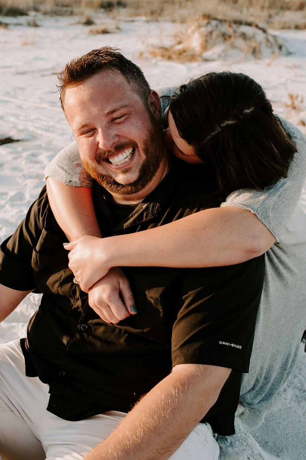 man laughing as his fiancé kisses him on the cheek during their north Florida engagement