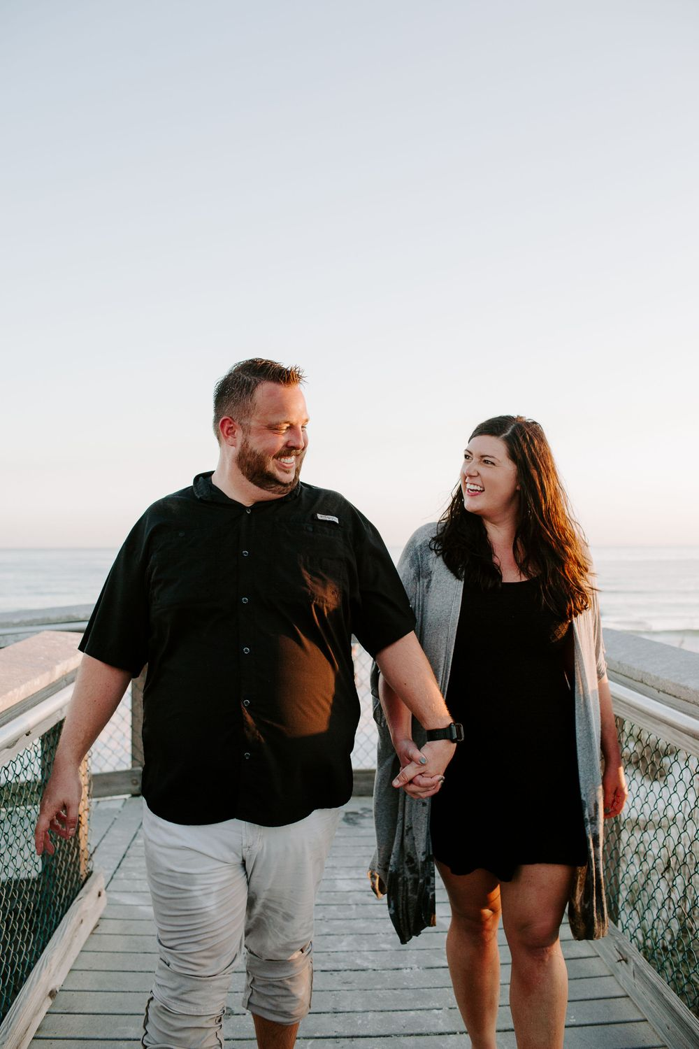 man and woman holding hands smiling at each other during their north Florida engagement
