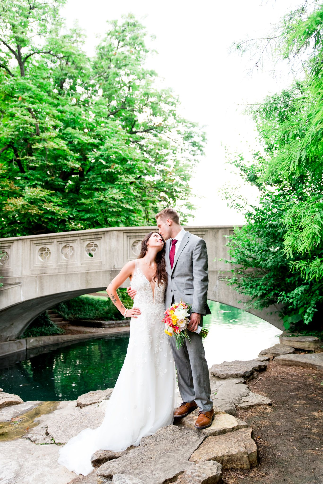 bride in Serafine gown and groom in gray suit holding pink and yellow bouquet looking at each other at Eden Park