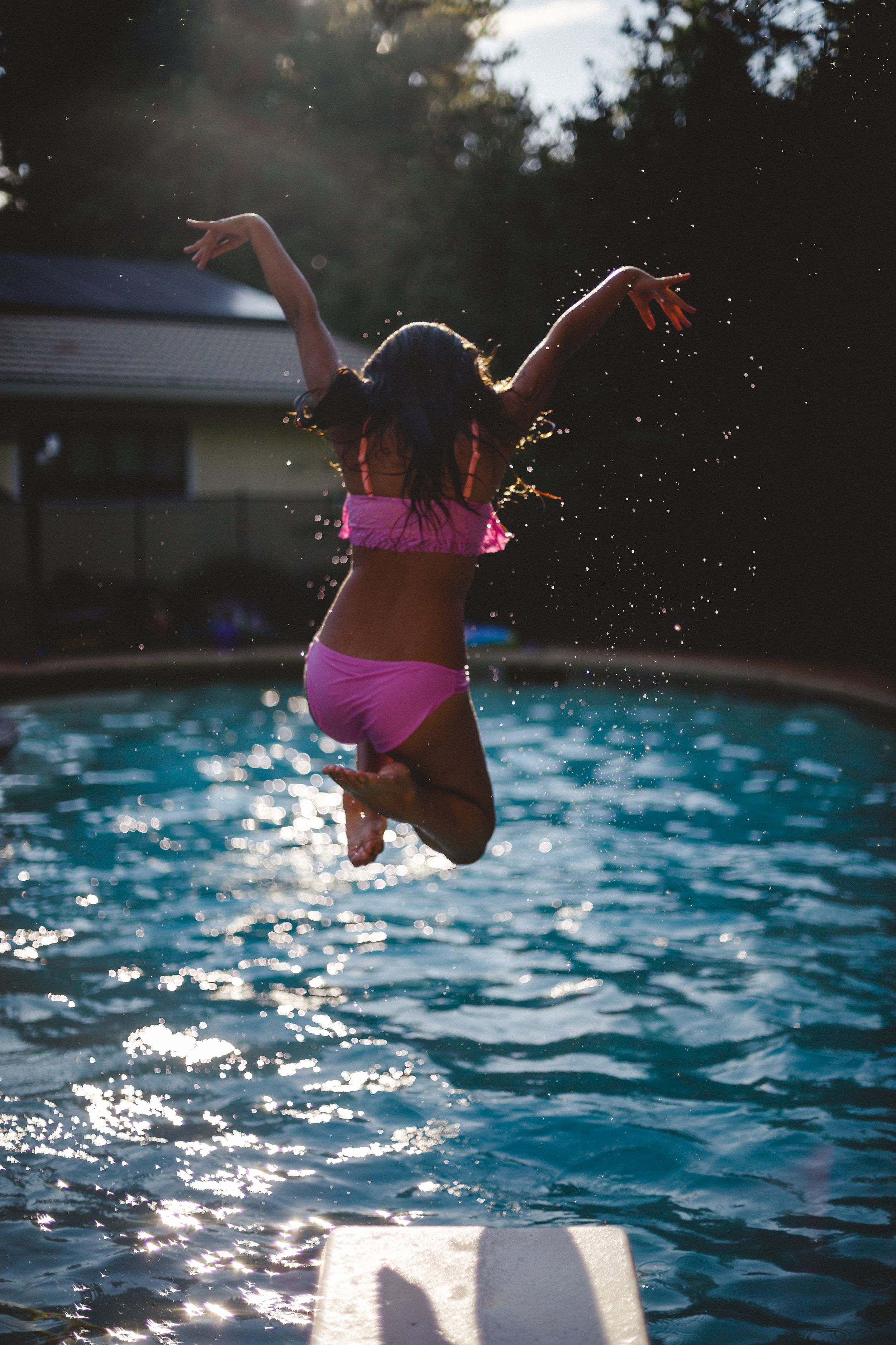 Girl jumping into a pool.