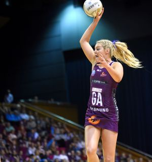 Netballer jumps with ball in hand