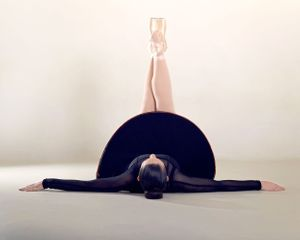 Ballerina lays on floor with arms out to side