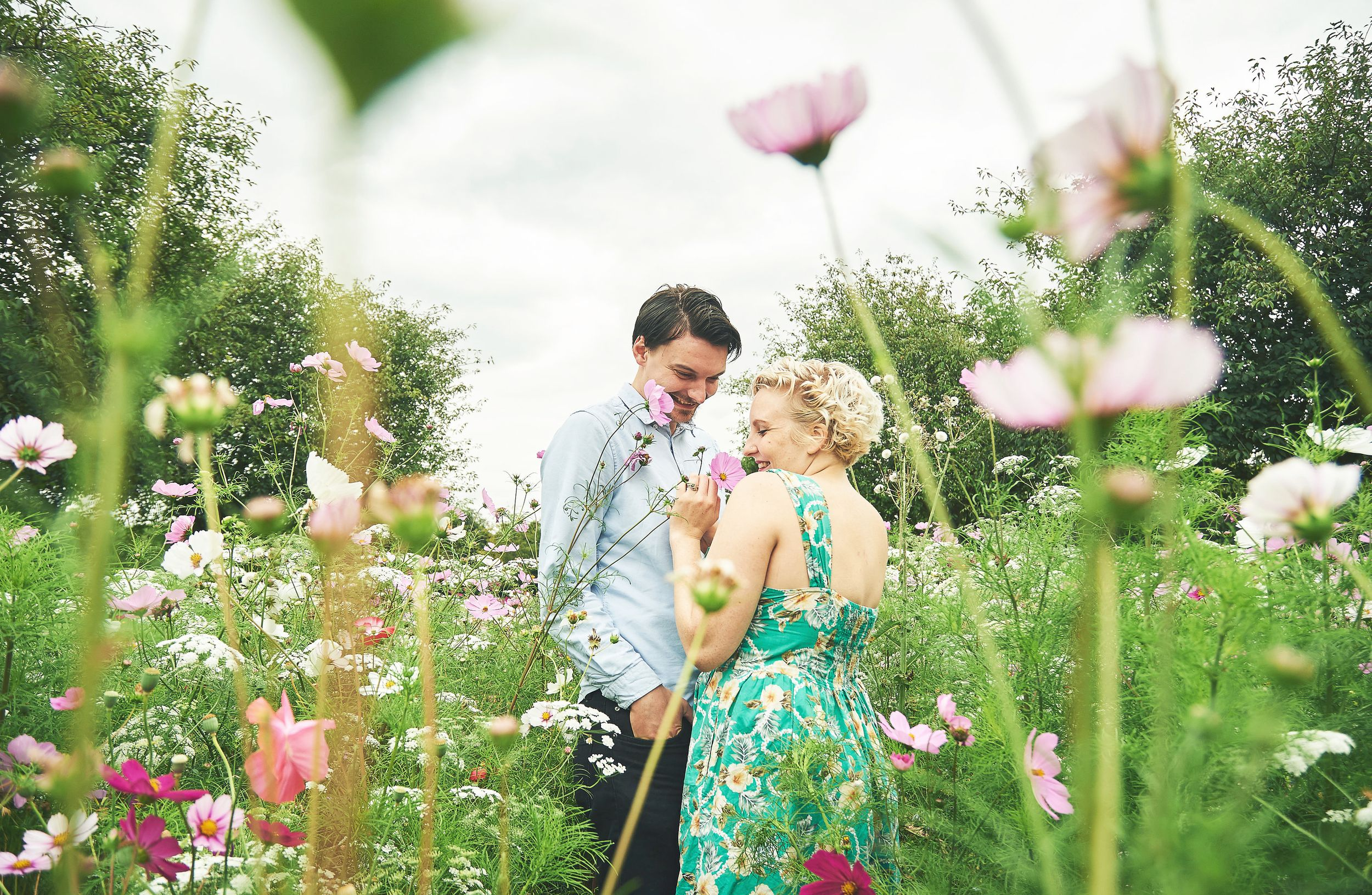 newly engaged couple stand in field on wildflowers by norfolk wedding photographer Faye Amare