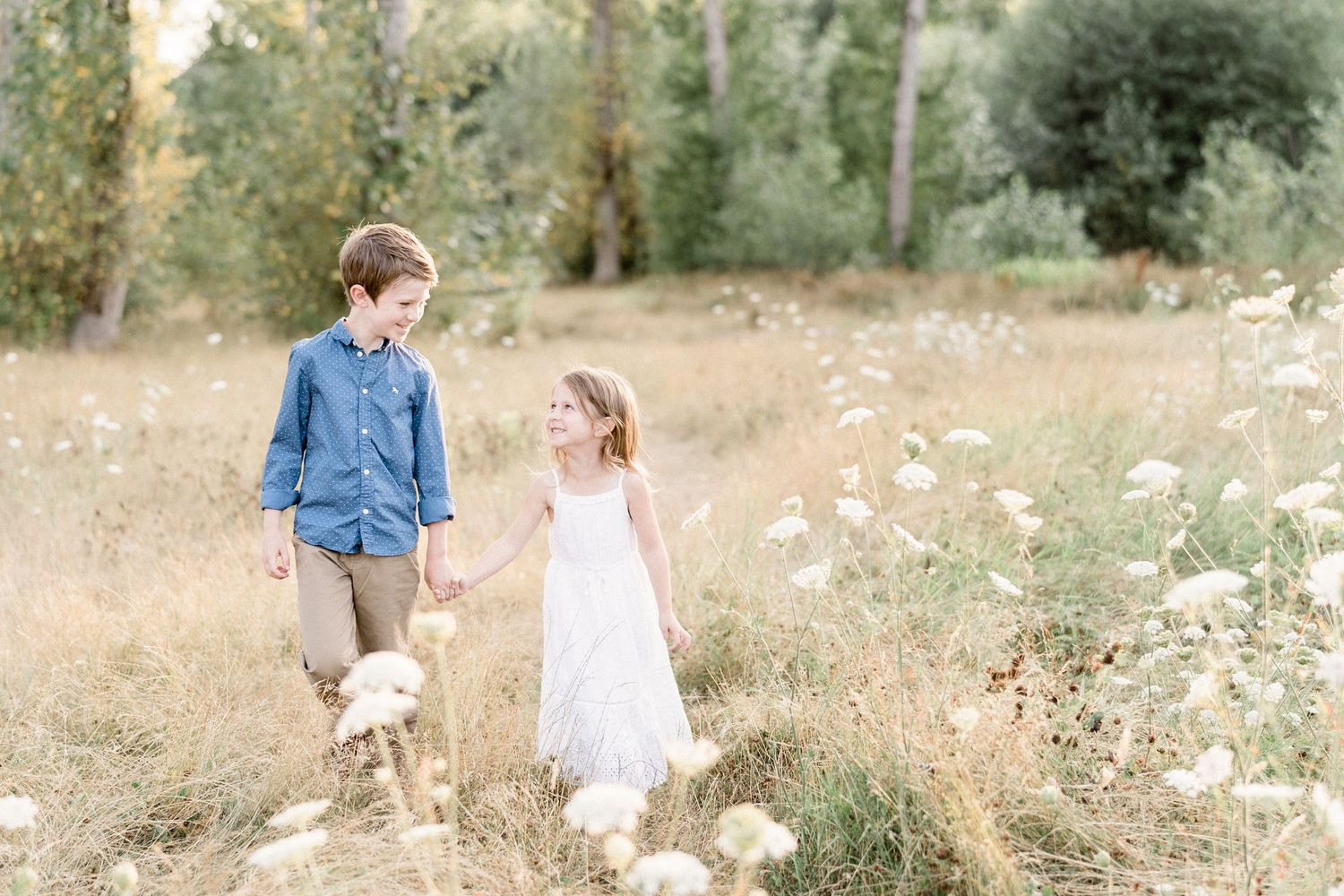 Brother and sister walking and smling at each other in a field of flowers