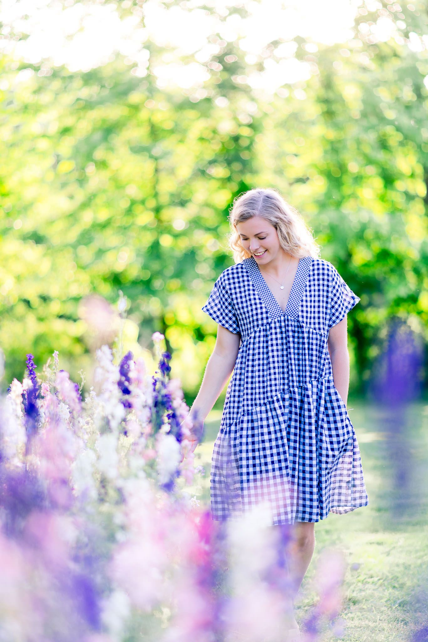 young woman in blue and white checkered dress smiling and looking at pink white and purple flower field