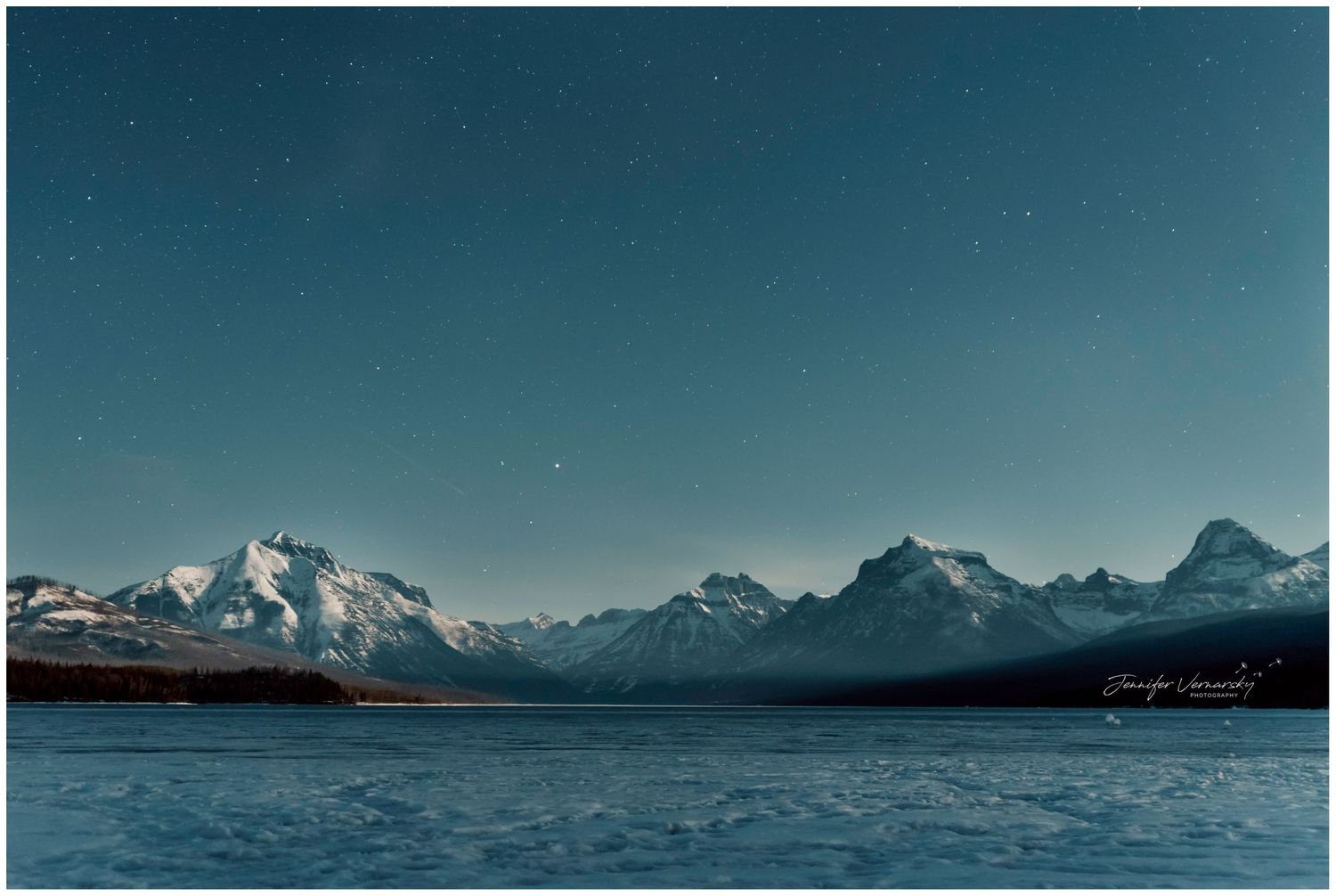 Frozen Lake McDonald at Glacier National Park, night sky with moon rising on the far right out of the image
