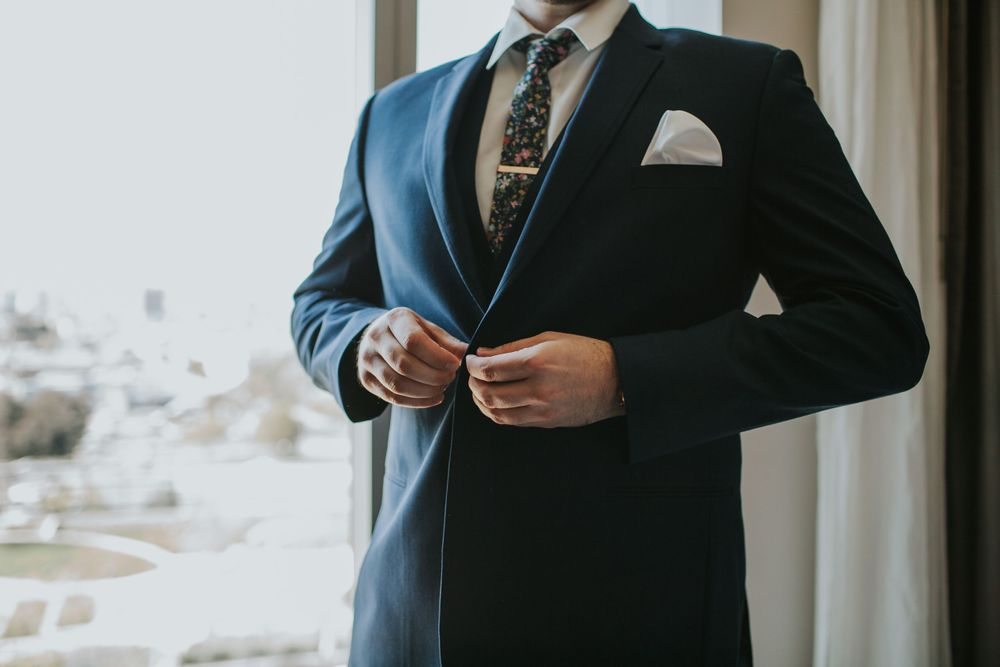 associate photographer photo of groom buttoning his jacket while getting ready