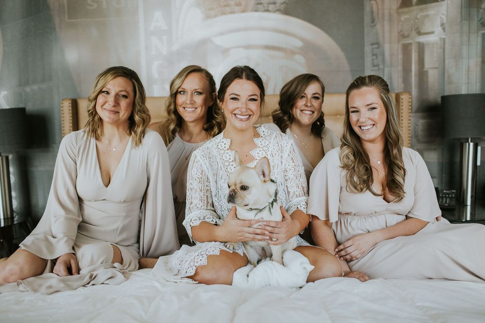 associate photographer photo of bride sitting on bed with her bridesmaids and dog