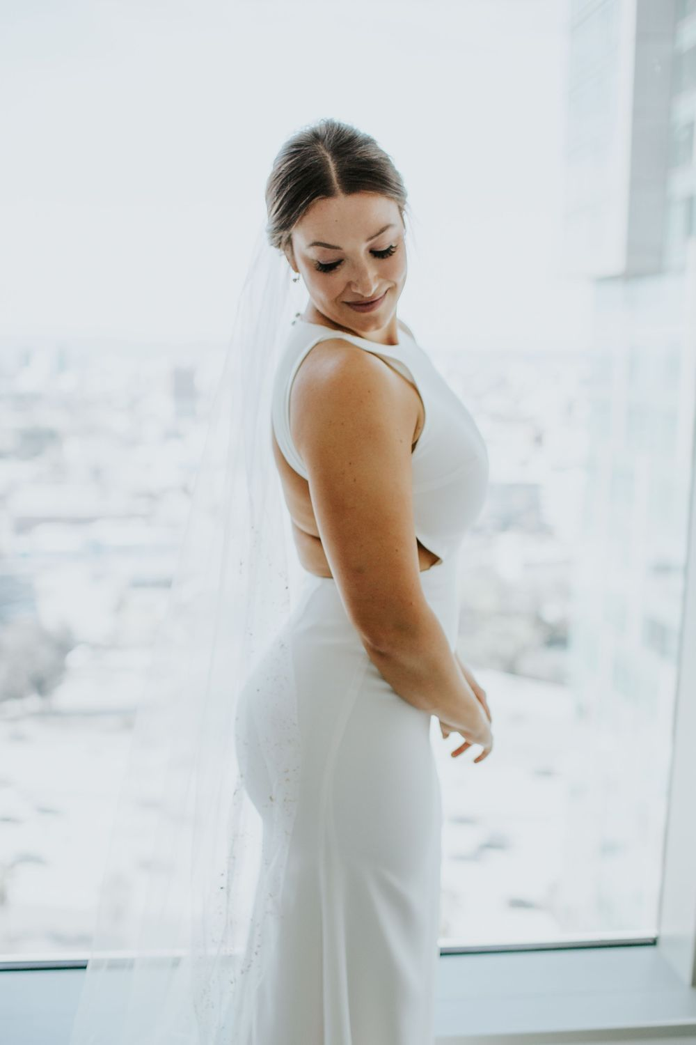 associate photographer photo of bride getting ready and admiring her dress