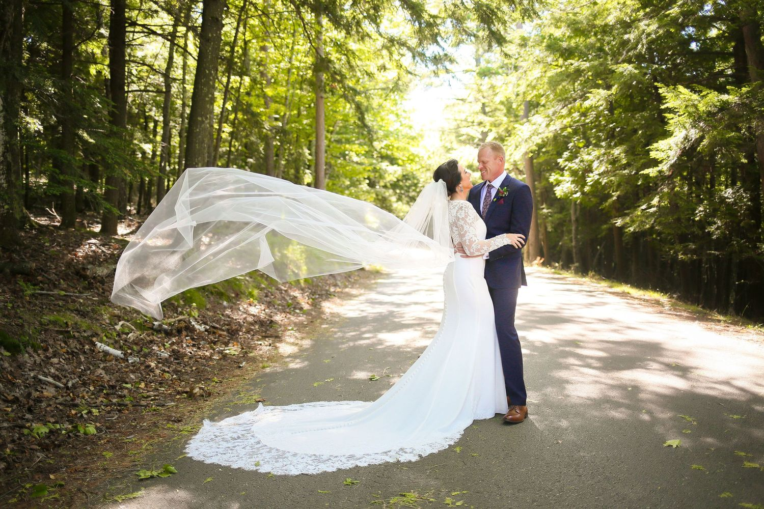 Bride and groom on Door County, WI path with veil flying in the wind for wedding photo by Laura Leigh Images