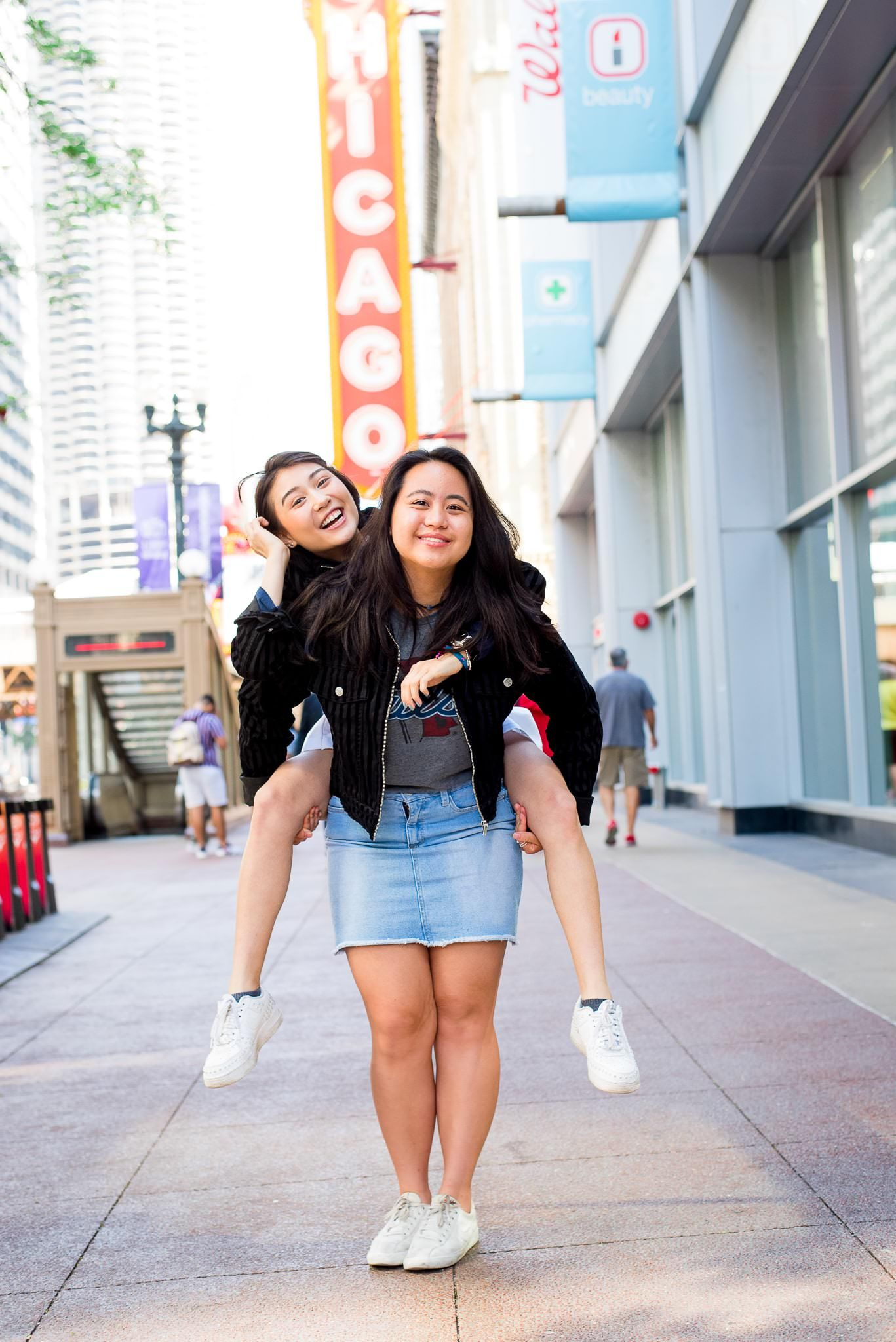 two senior girls in front of the Chicago Theater sign for Chicago senior pictures doing piggyback ride