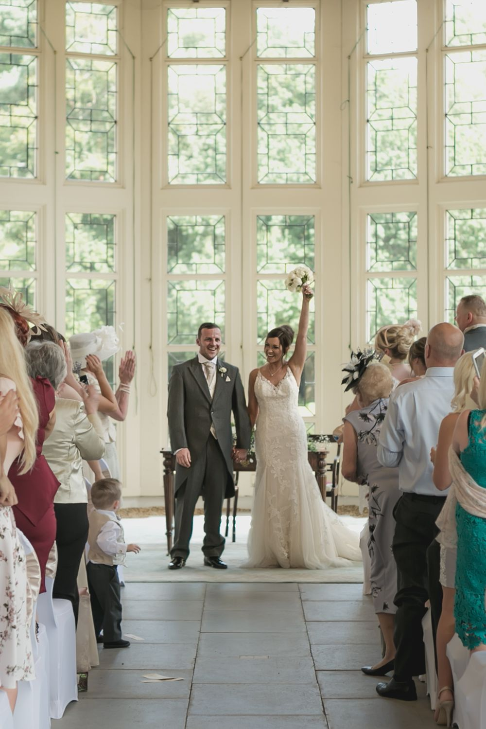 Bride holding her bouquet in the air after her ceremony at Highcliffe Castle